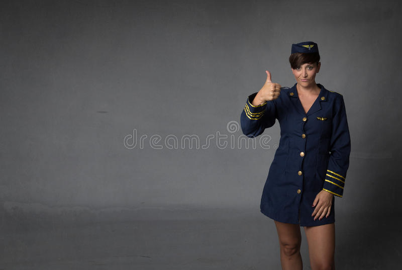 Air hostess thumbing up. Dark background stock images
