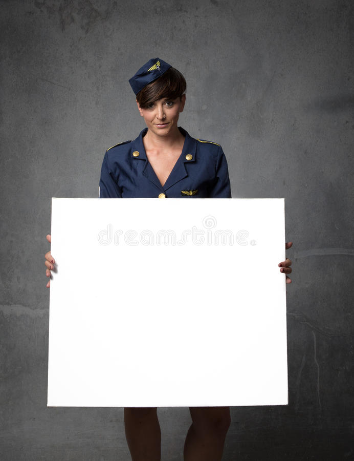 Air hostess with white empty board on hand. Dark background stock photo