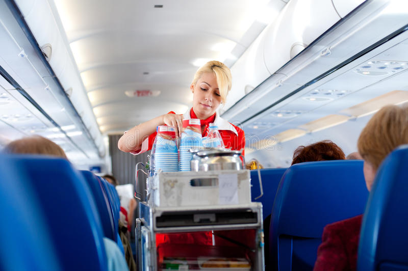 Air hostess at work. IRKUTSK - MOSCOW, RUSSIA - MAY 28: An unidentified air hostess of the airline Aeroflot serves drinks out on board of the flight from Irkutsk