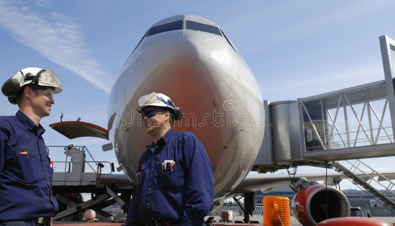 Air mechanics and airliner. Two mechanics with large airliner in background, airport activities stock photo