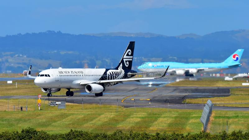 Air New Zealand Airbus A320 roulant au sol avec Korean Air Boeing 747-8i à l'arrière-plan à l'aéroport international d'Auckland photographie stock libre de droits