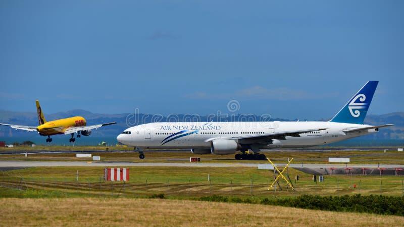 Air New Zealand Boeing die 777-200ER als DHL Tasman Ladingsluchtvaartlijnen Boeing 757 vrachtschipland taxi?en stock fotografie
