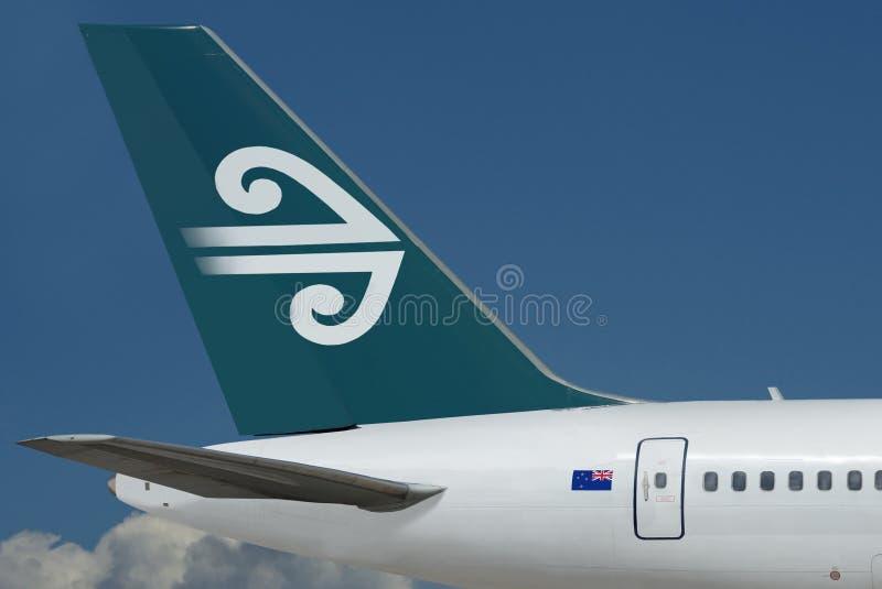 Air New Zealand-embleem op vliegtuig. Hemel, wolken stock foto's