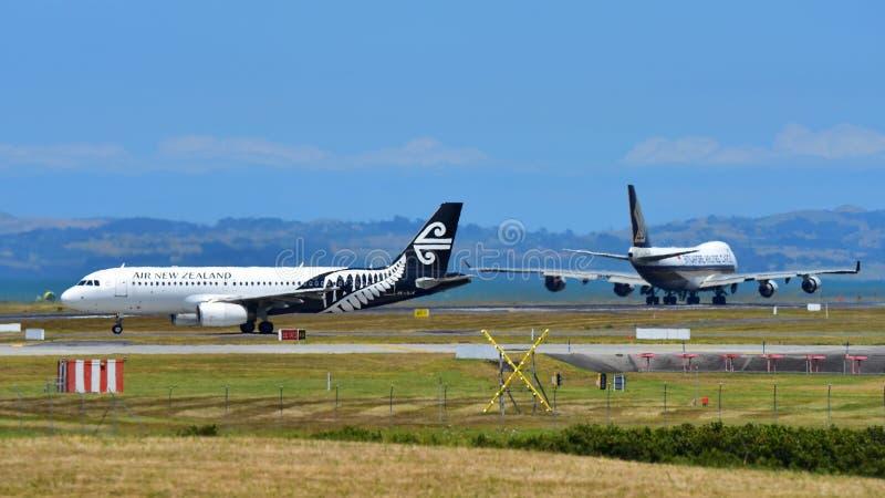 Air New Zealand flygbuss A320 som åker taxi, medan den Singapore Airlines Boeing 747-400 fraktbåten tar av på Auckland den intern royaltyfri foto