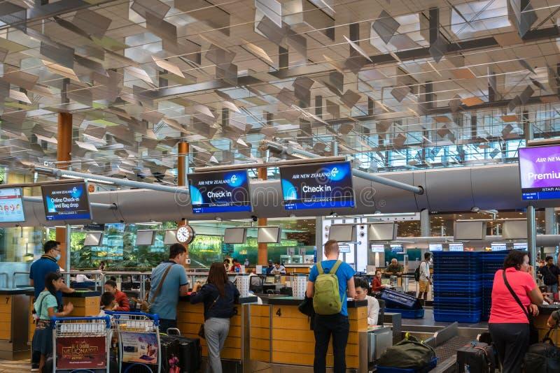 Air New Zealand incheckningsdisk med passagerare i den Singapore Changi flygplatsen royaltyfri bild
