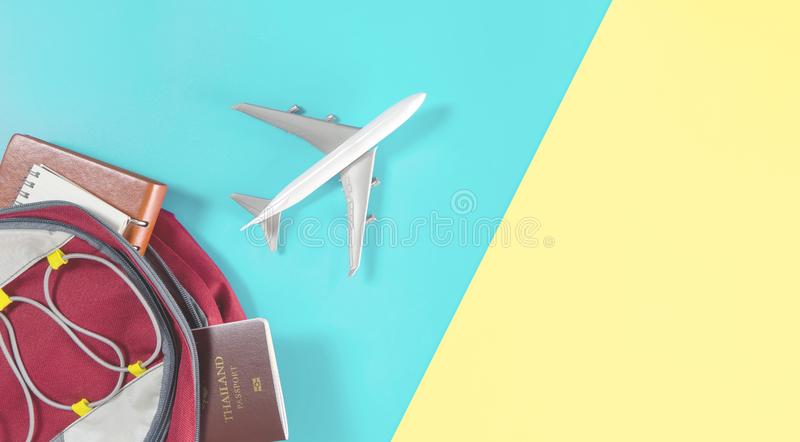 Air plane flying out of a traveler backpack accessories on blue yellow pink. Air plane is flying out of a traveler backpack accessories on blue yellow pink royalty free stock photos