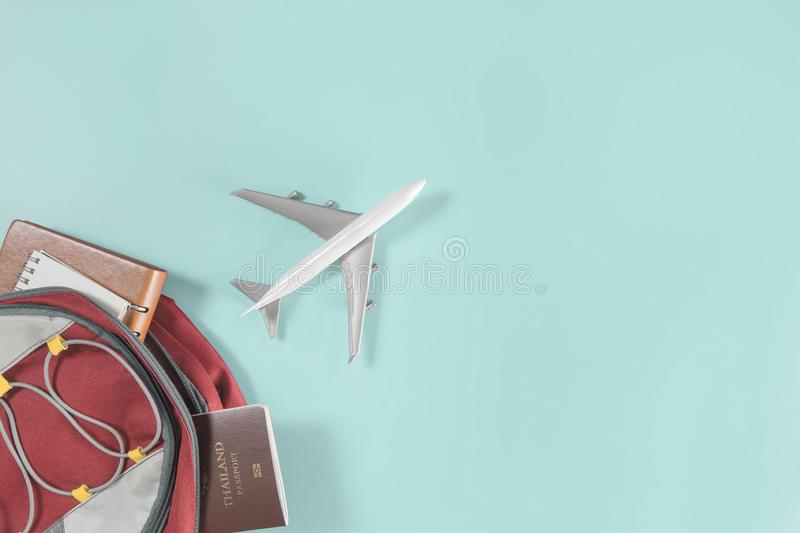 Air plane flying out of a traveler backpack accessories on teal. Air plane is flying out of a traveler backpack accessories on teal royalty free stock photos