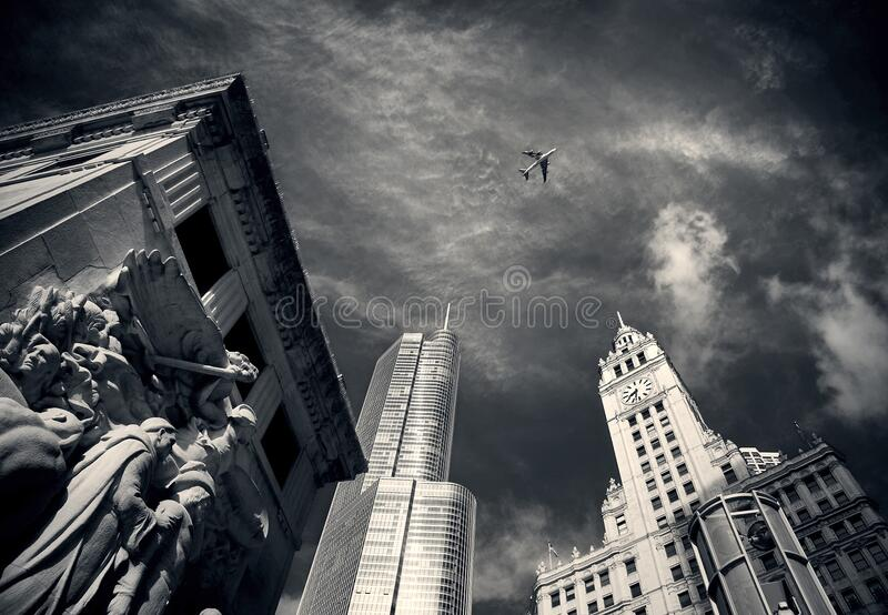 Air Plane Flying over Concrete Buildings and Statues in Grayscale Photography stock image