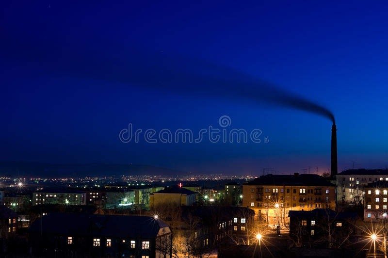 Air pollution. Tall smokestack belches smoke into sky over night city, copy space stock photos