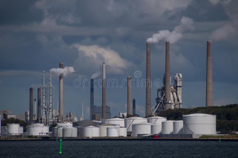 Air pollution from chimneys at industrial factory plant. Environmental impact: Tall chimneys letting out smoke and carbon dioxide at industrial factory plant stock photography