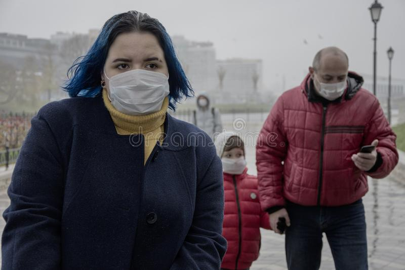 Air pollution in the city. Danger of airborne contamination. People in medical masks walking down the street. Air pollution in the city. Danger of airborne stock images