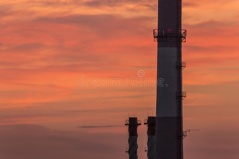 Air pollution in city environment, closeup of big industrial pipes at sunset royalty free stock photography
