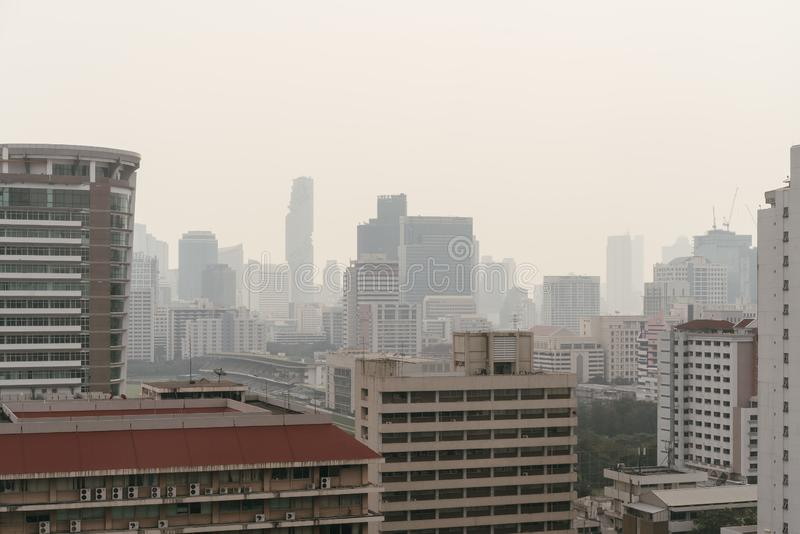 Air pollution effect made low visibility cityscape with haze and fog from dust in the air during sunset in Bangkok, Thailand royalty free stock photo