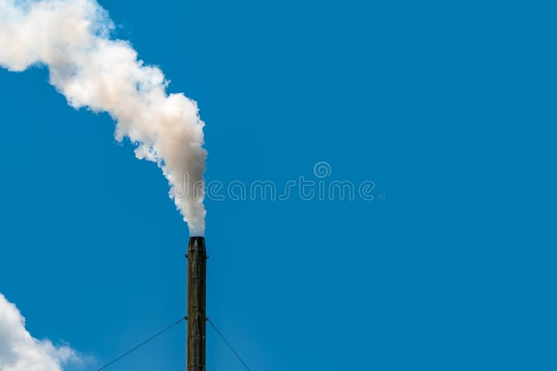 Air pollution from factory. Smoke from chimney of industrial pipe on clear blue sky. Greenhouse effect and global warming problem royalty free stock images