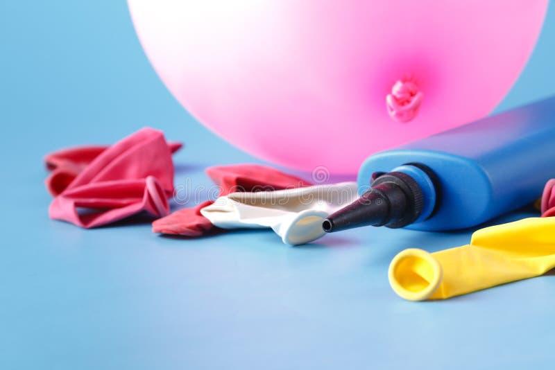 Air-pompe gonflant un ballon rose sur un fond bleu photos stock