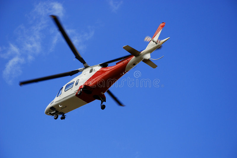 Air Rescue. Rescue helicopter lifting up in the air stock image