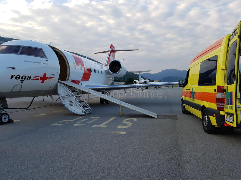 Air and road ambulance. Rega's Canadair 640 air ambulance transfering a patient to a road ambulance in Lugano, Switzerland, in May 2016 royalty free stock photo