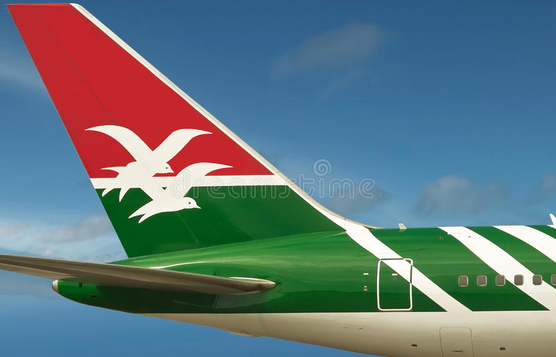 Air Seychelles plane. Thy logo of Air Seychelles airline company is on the tail of plane and is close-up on beautiful blue sky background. The sky area is free royalty free stock image