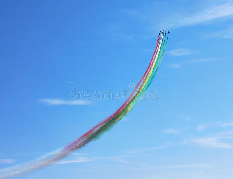 Air show. Air fighters on an air show flying in the shape of a geometric figure with colorful bright trails of smoke against a blue sky with clouds. Air stock image