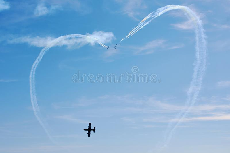 Air show. A figure in the sky in the shape of a heart from a smoke and ahead of an air fighter against a blue sky. Bright air show stock images