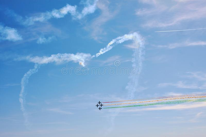 Air show. A figure in the sky in the shape of a heart from a smoke and ahead of an air fighter against a blue sky. Bright air show stock photo