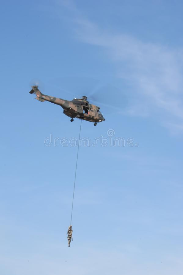 Air show. Soldier hanging from a helecopter at the Swartkop air show in Pretoria, South Africa royalty free stock photos