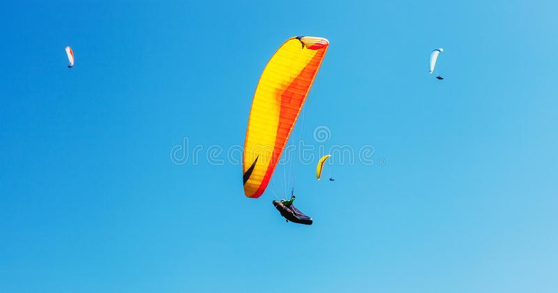 Air sportsmans group soaring in sky with a bright paraplanes stock images