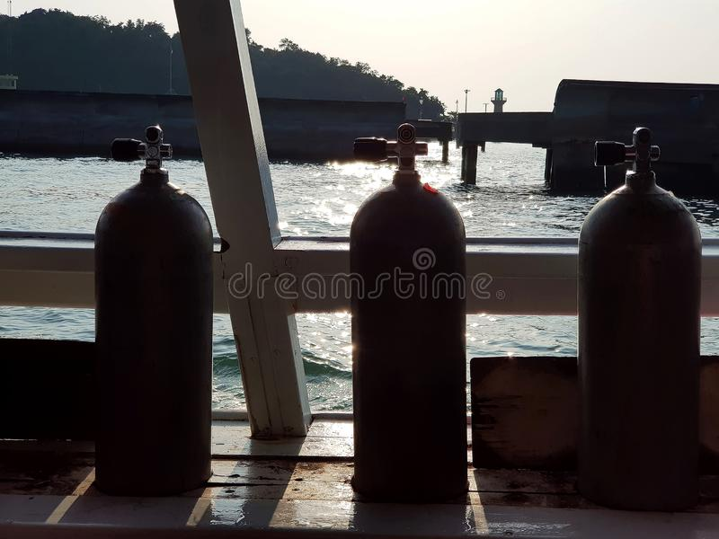 Air tanks in the slots for SCUBA divers on the boat, silhouette royalty free stock image