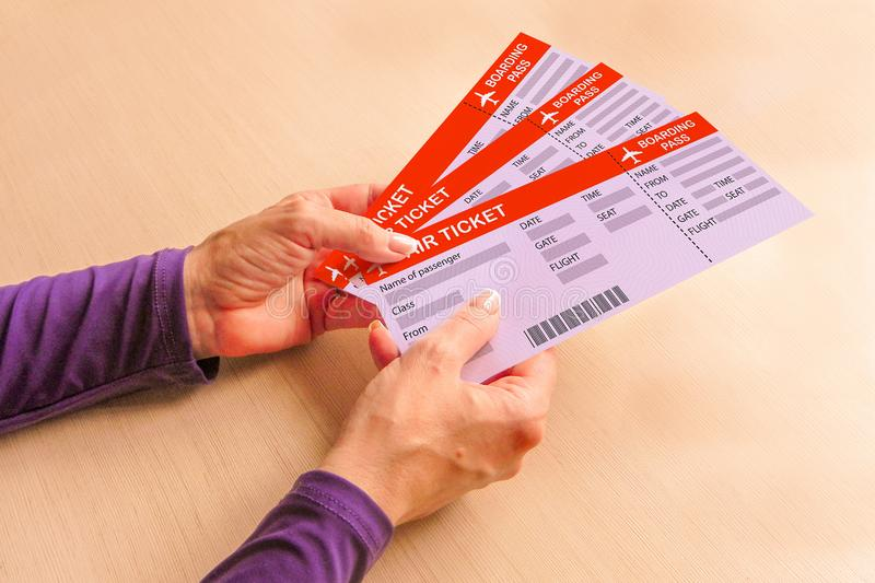 Air tickets and boarding passes in hands of old woman. Travel after retirement and pension. Elderly middle aged people going to royalty free stock photography