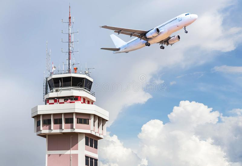 Air traffic control tower in international airport with passenger airplane jet taking off. On blue sky background royalty free stock photography