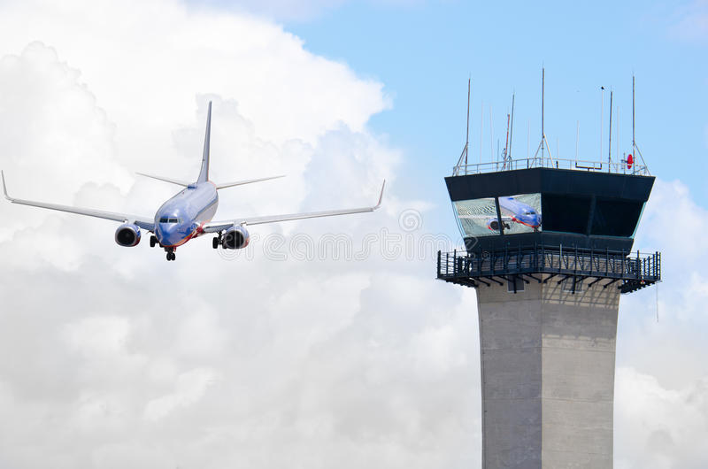 Air traffic control tower with jet airplane. Closeup of an air traffic control tower with a jumbo jet airliner coming in for a landing. The plane is reflecting stock photo