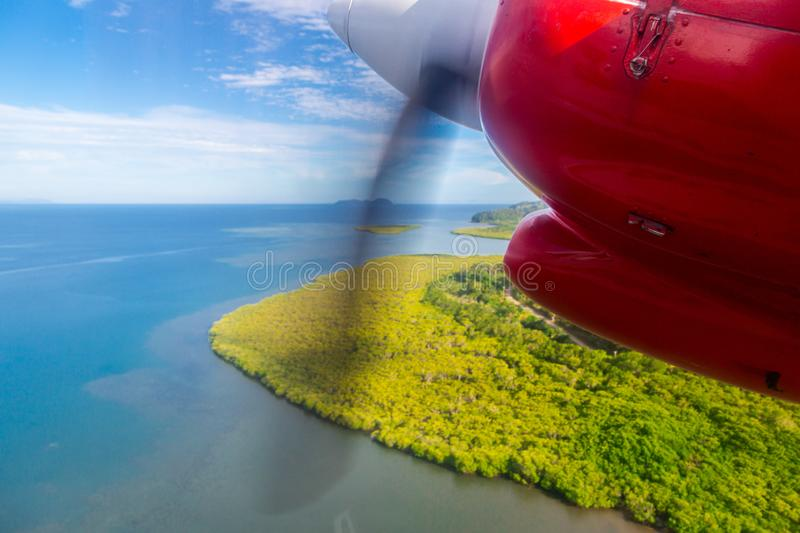 Air travel in Fiji, Melanesia, Oceania. View of a green remote tropical island from a window of a small propeller airplane. Air travel in Fiji, Melanesia royalty free stock image
