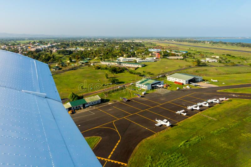 Air travel in Fiji, Melanesia, Oceania. View of hangars, helicopters and small planes on Nausori Suva International Airport apron. Air travel in Fiji, Melanesia royalty free stock images