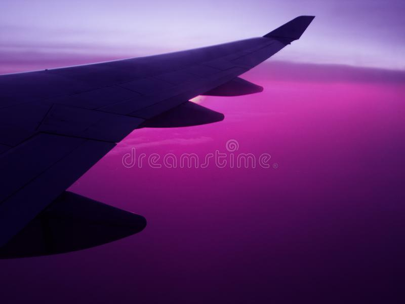 Air travel plane wing wih violet sky. Air travel abstract plane wing with saturated sunset violet or purple sky royalty free stock image