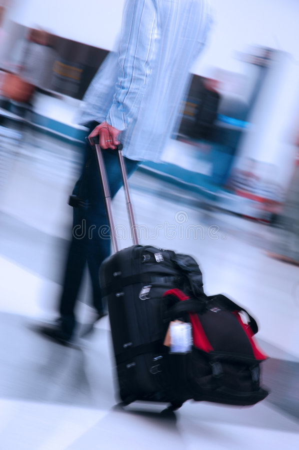 Air Traveler. Man pulling suitcase through a busy airport royalty free stock photography