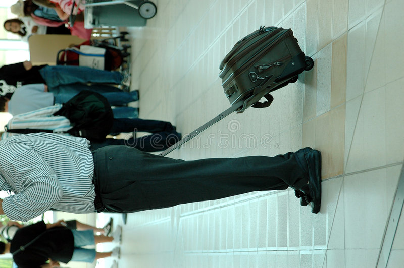 Air Traveler. A business man with suitcase in an airport from the shoulders down royalty free stock photography