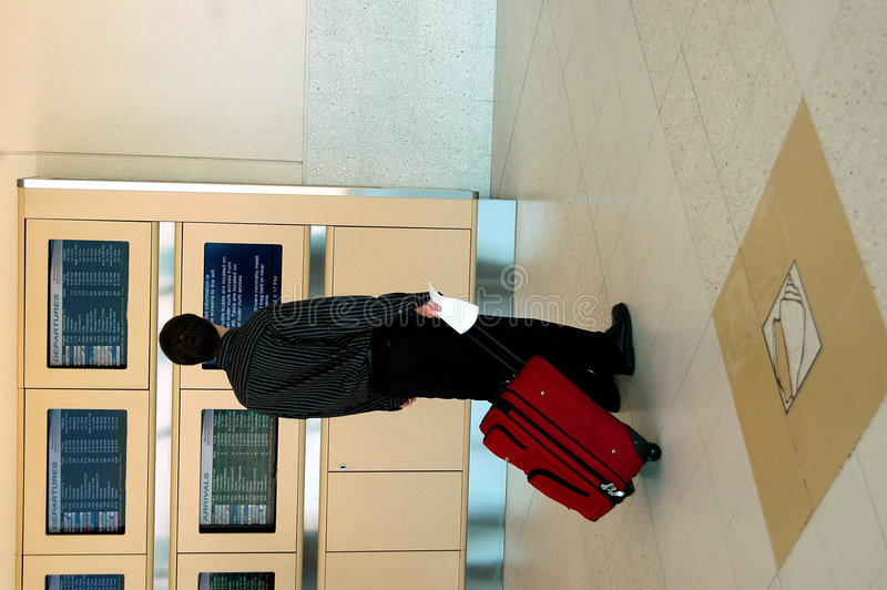 Air Traveler. A businessman with a suitcase checking the flight status on board in an airport stock photo