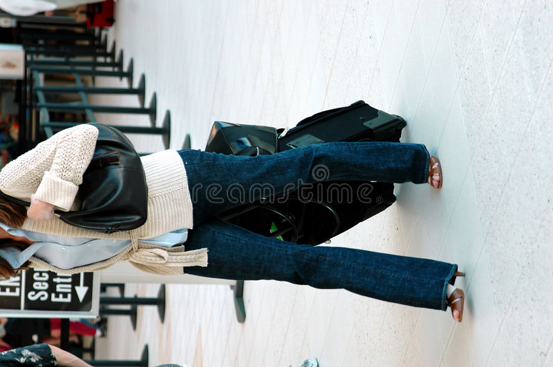 Air Traveler. A stylish woman with suitcase in an airport from the shoulders down stock photos
