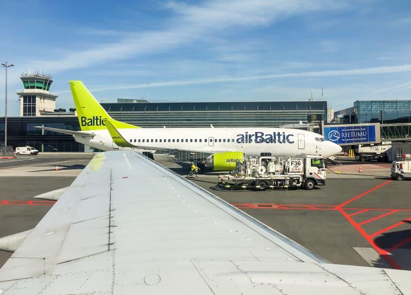 AirBaltic-Vliegtuigenvoorbereiding voor vertrek in de Internationale Luchthaven van Riga stock foto