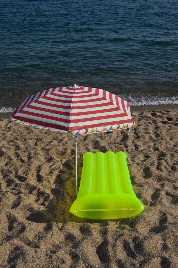 Airbed und Sonneregenschirm auf einem Strand lizenzfreies stockbild