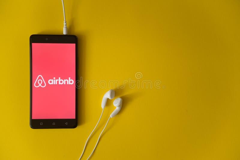 Airbnbembleem op het smartphonescherm op gele achtergrond stock afbeeldingen