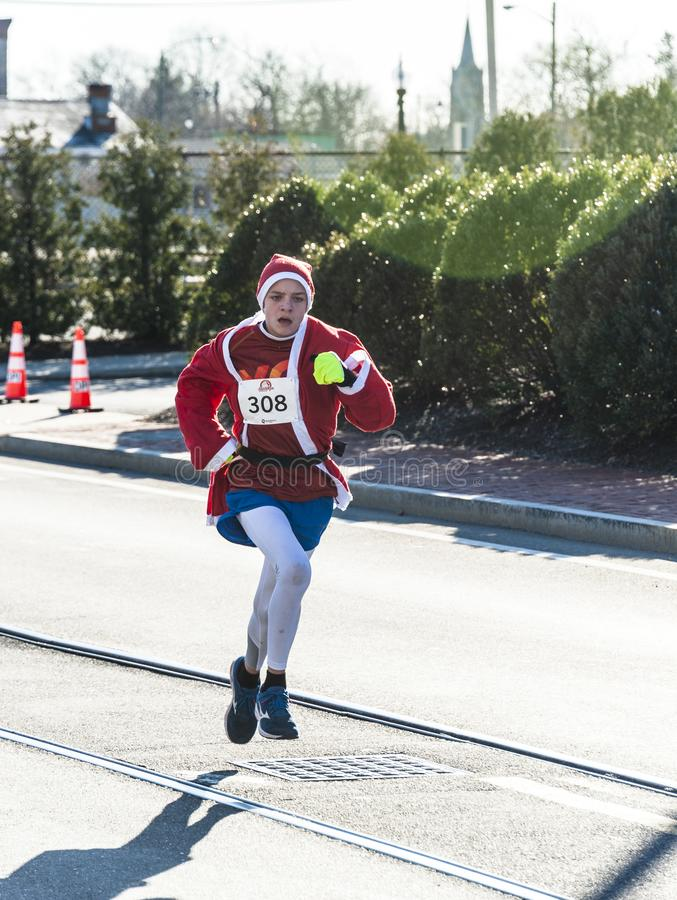 Airborne Santa. New Bedford, Massachusetts, USA - December 8, 2018: Runner-up Santa bounds toward the finish of the Santa Sightings 5K Fun Run along the New royalty free stock photos
