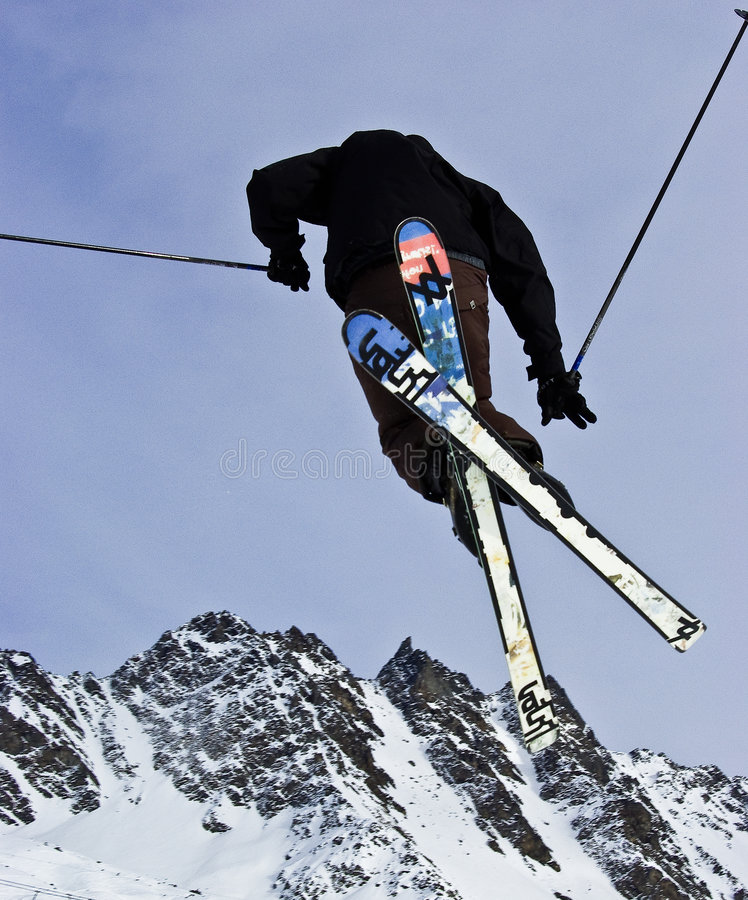 Airborne Skier. From viewpoint underneath and slightly behind the skier, with view of Verbier, Switzerland mountains royalty free stock photo