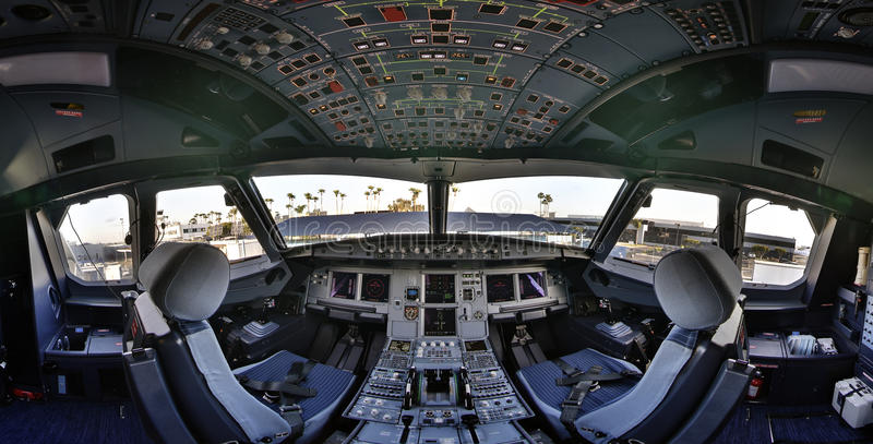 Airbus 320 cockpit flightdeck. Fisheye view of the cockpit (flightdeck) of an Airbus 320 commercial jet aircraft on the ground in california with palm trees in stock photo
