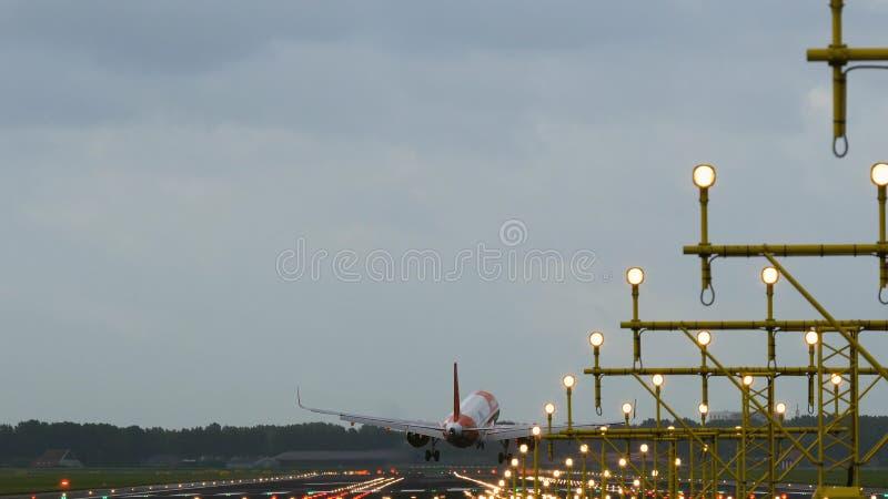 Airbus A320 de las tierras fáciles de las líneas aéreas del jet en pista iluminada fotos de archivo