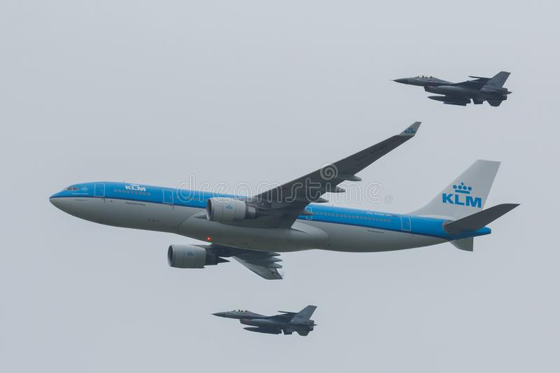 Airbus A330 of the KLM escorted by two F-16 of the Royal Dutch Airforce royalty free stock images