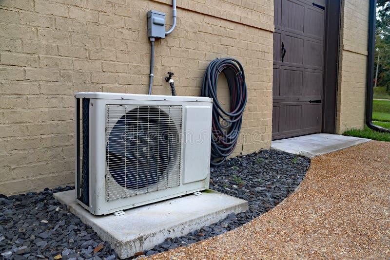 Airconditioner mini gespleten systeem naast huis met bakstenen muur royalty-vrije stock afbeeldingen
