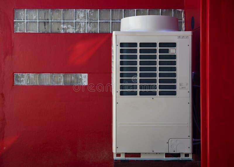 Airconditionercompressor in de rode muurbouw die wordt geïnstalleerd stock afbeeldingen