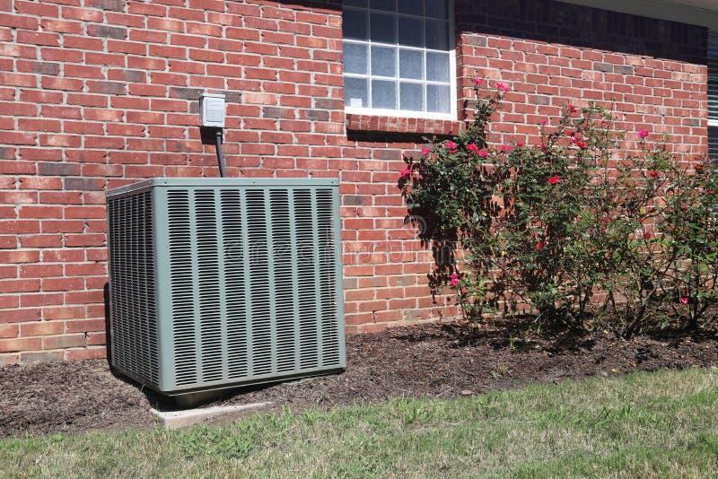Airconditionereenheid bij een huis met roze struiken stock afbeelding