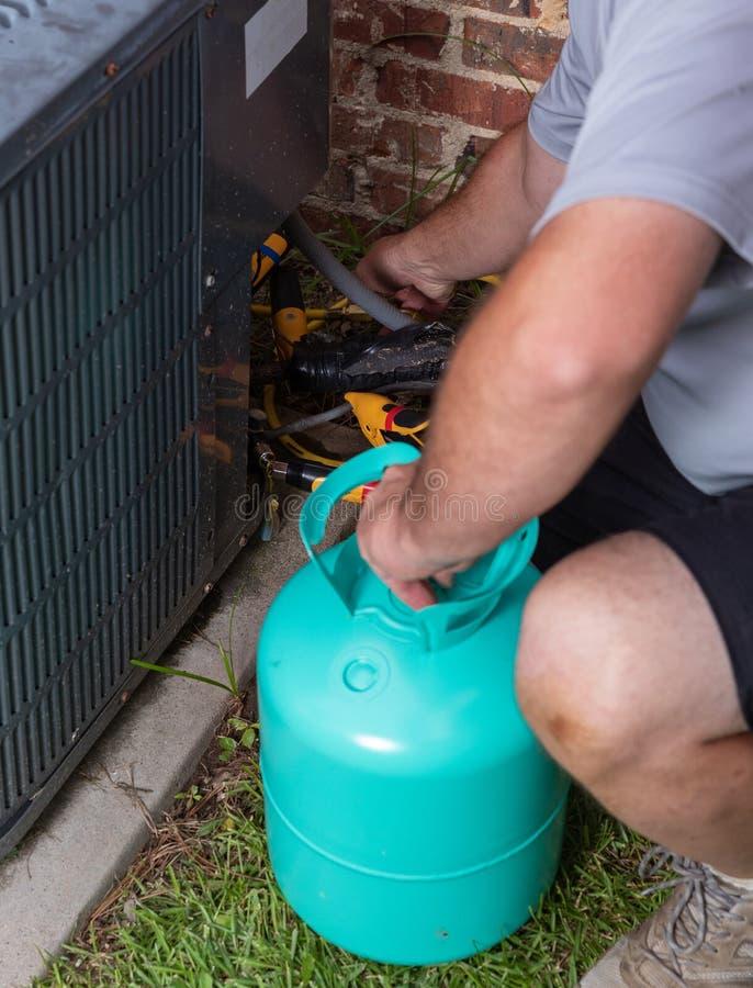 Airconditioneronderhoud met technicus die koelmiddel toevoegen stock foto